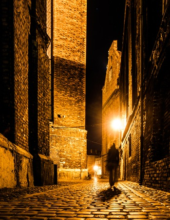 Photo for Cobbled street of Old Town with dark blurred silhouette of person. Evokes Jack the Ripper. - Royalty Free Image