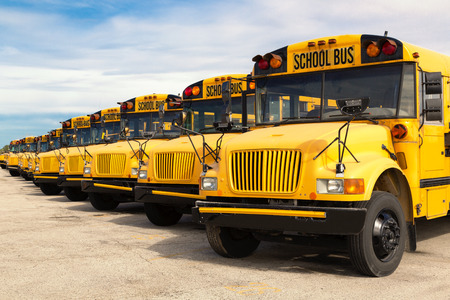 Photo pour row of yellow school buses lined up in a parking lot - image libre de droit