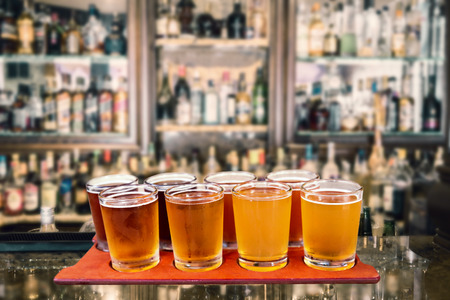 Photo pour Beer flight of eight sampling glasses of craft beer on a serving board in a bar. - image libre de droit