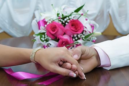 Foto de the hands of the newlyweds and bridal bouquet on the table - Imagen libre de derechos