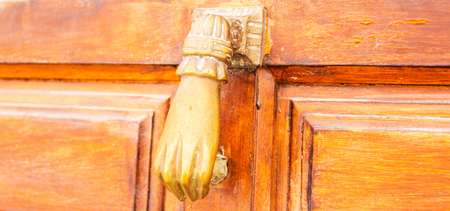Photo pour Door with brass knocker in the shape of a hand,  beautiful entrance to the house, vintage decoration - image libre de droit