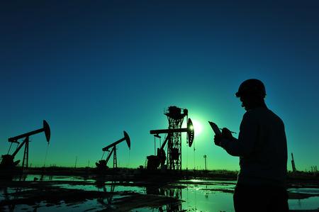 Photo pour Oil field oil workers at work - image libre de droit
