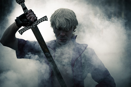 Photo pour portrait of a brutal warrior with sword in smoke - image libre de droit