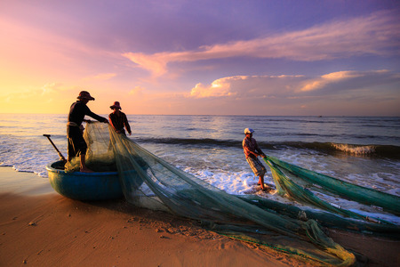Foto de Beach Lagi, Binh Thuan province, Vietnam - August 29, 2015: Unknown Fishermen who pull up th are the fishing nets khi sunrise. This is ask for their daily work - Imagen libre de derechos