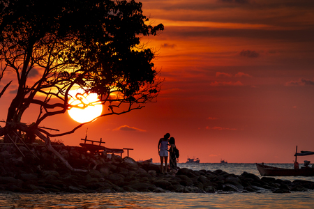 Foto de The silhouette of couple enjoyed the sunset of Koh Rong samloem island in Cambodia in paradise island Villa Koh Rong Samloem. Cambodia. This is a small island that attracts many visitors from all over - Imagen libre de derechos