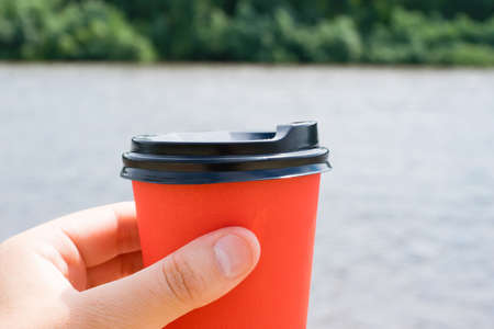 Coffee paper cup in a woman's hand on the beach on a summer sunny day.