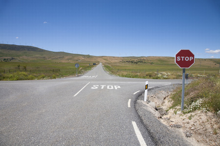 crossroad with stop symbol painted on asphalt and red hexagonal signal metal pole in rural road next to Madrid Spain Europe