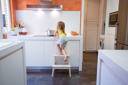 Foto de Four years old blonde child climbing on stool o ladder to cook in electrical cooktop with a saucepan, alone in the kitchen - Imagen libre de derechos