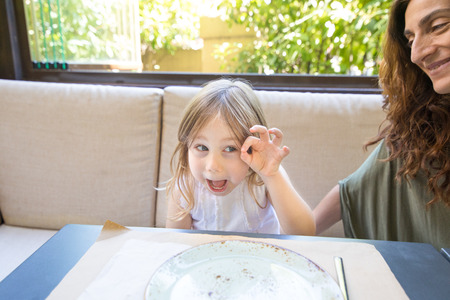 Photo for Funny expression and gesture. Four years age blonde happy girl teasing and grimacing next to woman mother smiling sitting in restaurant - Royalty Free Image