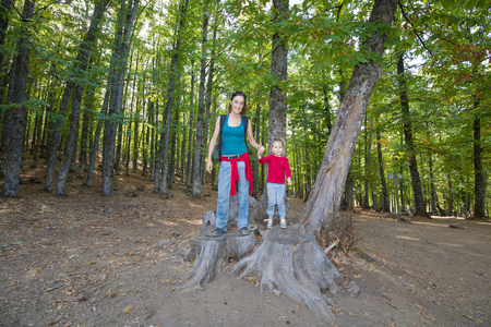 Foto de mother woman and four years age blonde child standing on cut tree trunk posing smiling in forest of chestnut in autumn - Imagen libre de derechos
