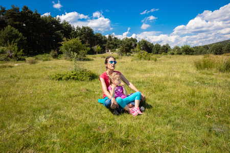 Foto de little daughter, four years old girl, resting sitting on her mother legs in a grass meadow of the country in Canencia mountain (Madrid, Spain, Europe) - Imagen libre de derechos