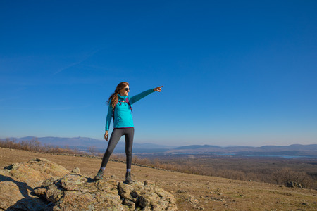 Foto de hiker or trekking woman standing on rock, pointing with hand to a text or copy space in blue sky, in Guadarrama Natural Park (Madrid, Spain) - Imagen libre de derechos