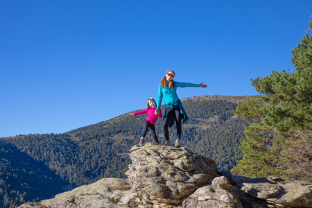 Foto de mountaineer happy family (woman and five years old girl) posing on the top of rock in mountain of Fuenfria Valley, in Guadarrama Natural Park (Cercedilla, Madrid, Spain) - Imagen libre de derechos