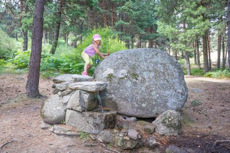 Foto de five years old blonde girl walking on rocks and above a fountain, on summer, in a forest in Guadarrama Natural Park (Madrid, Spain, Europe) - Imagen libre de derechos