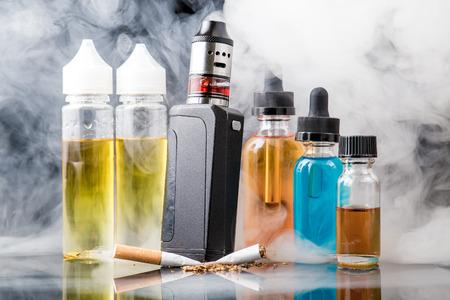 Foto de Modern vaporiser versus old tobacco cigarette in smoke cloud - Imagen libre de derechos