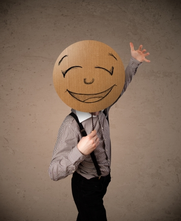 Photo for Businessman holding a cardboard smiley face emoticon in front of his head - Royalty Free Image