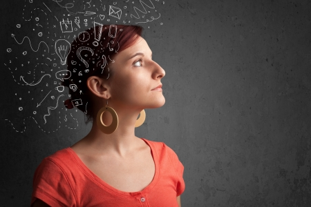 Foto de Young girl thinking with abstract icons on her head - Imagen libre de derechos