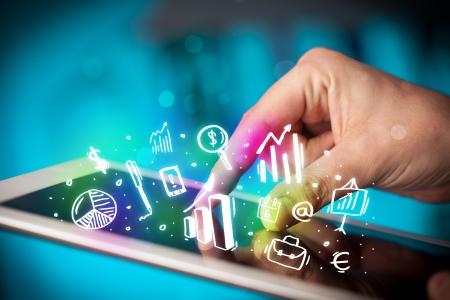Foto de Finger pointing on tablet pc, charts concept - Imagen libre de derechos