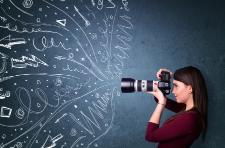 Photo for Photographer girl shooting images while energetic hand drawn lines and doodles come out of the camera - Royalty Free Image