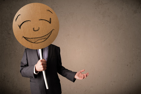 Photo pour Businessman holding a cardboard smiley face emoticon in front of his head - image libre de droit