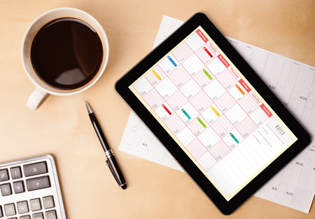 Photo pour Workplace with tablet pc showing calendar and a cup of coffee on a wooden work table close-up - image libre de droit