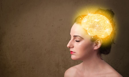 Foto de Young girl thinking with glowing brain illustration on grungy background - Imagen libre de derechos