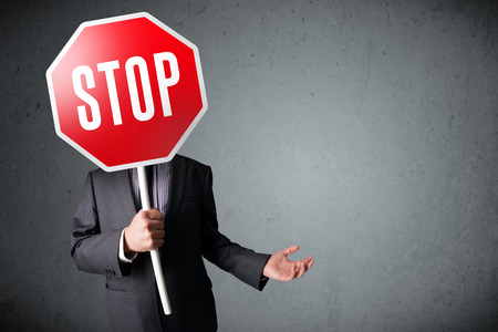 Photo pour Businessman standing and holding a stop sign in front of his head - image libre de droit