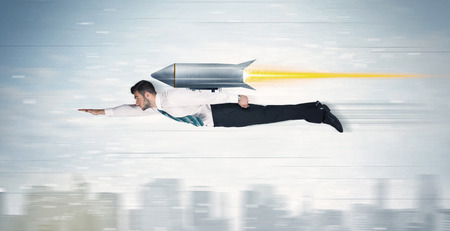 Foto per Superhero business man flying with jet pack rocket above the city concept - Immagine Royalty Free