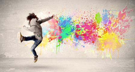 Foto de Happy teenager jumping with colorful ink splatter on urban background concept - Imagen libre de derechos