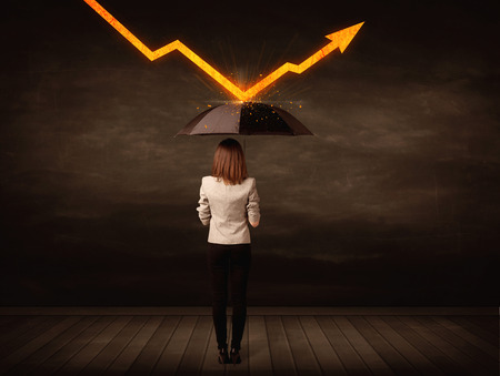 Foto de Businesswoman standing with umbrella keeping orange arrow concept on background - Imagen libre de derechos