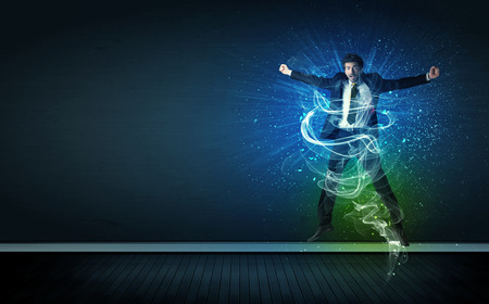 Photo pour Talented cheerful businessman jumping with glowing energy lines on background - image libre de droit