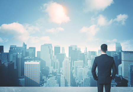 Photo for Businessman standing on a roof and looking at future city - Royalty Free Image