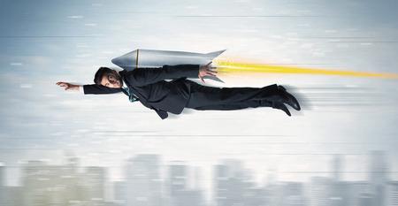 Photo pour Superhero business man flying with jet pack rocket above the city concept - image libre de droit