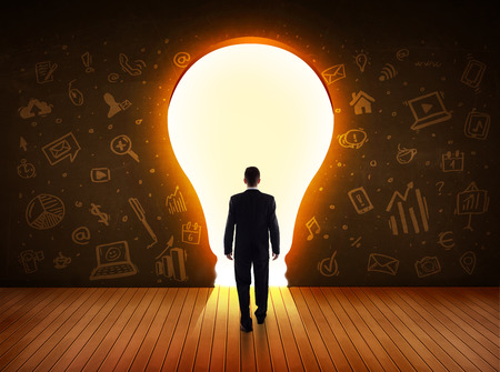 Photo pour Business man looking at bright light bulb in the wall concept - image libre de droit