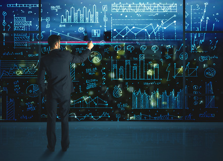 Foto de Businessman drawing business statistics on glass wall - Imagen libre de derechos