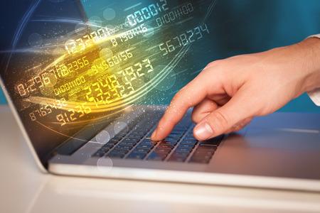 Foto de Man typing on modern notebook with future number technology data coming out - Imagen libre de derechos