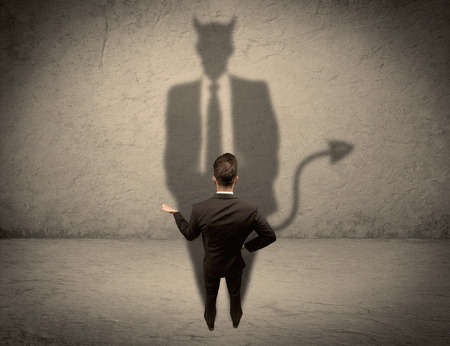 Photo pour An experienced tricky businessman in suit looking at his devil desguise shadow reflected on the wall concept - image libre de droit
