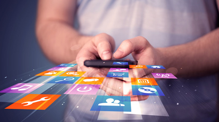 Photo for Man holding smart phone with colorful application icons comming out - Royalty Free Image