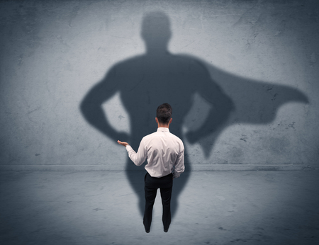 Photo pour A confident young elegant salesman with briefcase facing a wall, looking at his super man shadow concept - image libre de droit