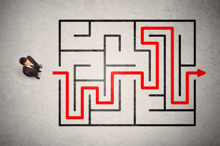 Foto de Lost businessman found the way in maze with red arrow on grungy background - Imagen libre de derechos