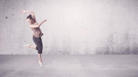 Foto de A beautiful young hip hop dancer dancing contemporary urban street dance in empty clear grey wall background concept. - Imagen libre de derechos