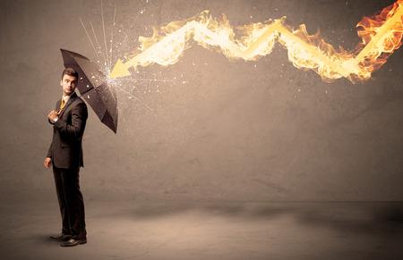 Foto de Business man defending himself from a fire arrow with an umbrella on grungy background - Imagen libre de derechos