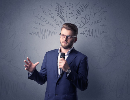 Businessman speaking into microphone with scribbles over his head