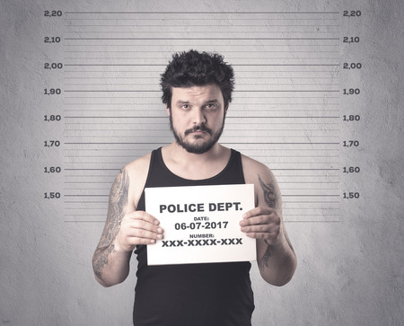 Photo for Caught gangster in jail with table on his hand. - Royalty Free Image