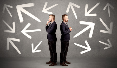 Photo pour Young conflicted businessman choosing between two directions with arrows around him - image libre de droit