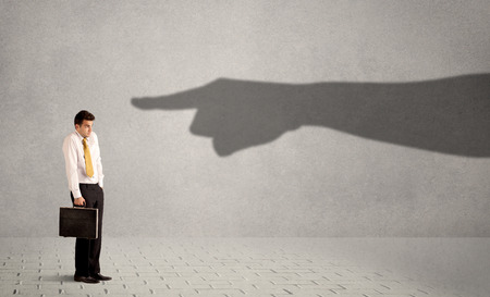 Foto de Business person looking at huge shadow hand pointing at him concept on background - Imagen libre de derechos