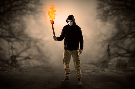 Photo for Man coming out from a thicket with burning flambeau - Royalty Free Image