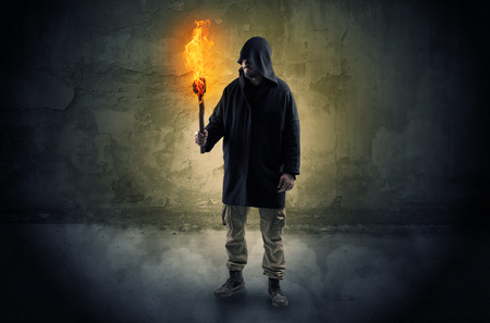 Photo for Wayfarer with burning torch in front of crumbly wall concept - Royalty Free Image