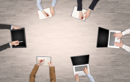 Photo for Group of people with devices in hands having desk discussion and making reports together on laptop, tablet, notebook  - Royalty Free Image