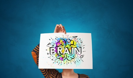 Photo pour Young person holding white paper in front of her head with colorful brain concept - image libre de droit
